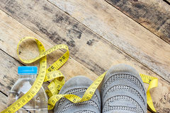 Yellow measuring tape, sport shoes and water on wooden table Royalty Free Stock Photo
