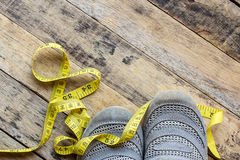 Yellow measuring tape and sport shoes on wooden table Stock Images