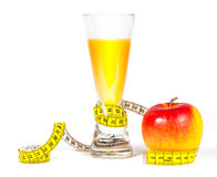 A yellow measuring tape wrapping red apple and juice Royalty Free Stock Photography