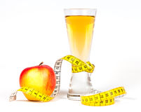 A yellow measuring tape wrapping red apple and juice Stock Image