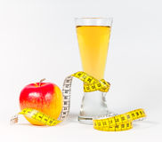 A yellow measuring tape wrapping red apple and juice Stock Photo