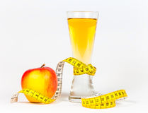 A yellow measuring tape wrapping red apple and juice Stock Images