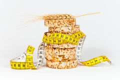 A yellow measuring tape wrapping sheaf of wheat and rice cakes Stock Photos