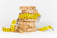 A yellow measuring tape wrapping sheaf of wheat and rice cakes Stock Image