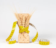 A yellow measuring tape wrapping wheat cracker or crispbread Royalty Free Stock Images