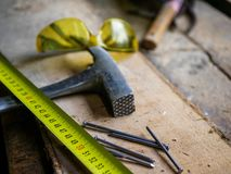 Yellow measurment tape, hammer, nails, protection eyeglass. On cracked wooden workbench stock image