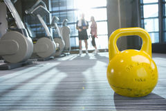 Yellow medicine ball on floor in health club with couple in background Royalty Free Stock Image