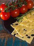 Yellow medium-hard mild Swiss cheese Emmental, fresh rosemary an Stock Photography