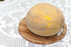 Yellow melon on the kitchen wooden board Stock Image