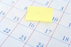 Yellow memo note on a calendar Stock Image