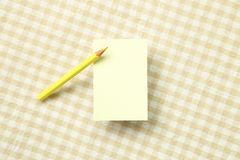 Yellow memo note pad and yellow colored pencil on beige fabric background. Yellow memo note pad and yellow colored pencil on beige check pattern fabric stock photography