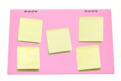 Yellow memo stick on Pink calendar Royalty Free Stock Image