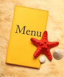 Yellow menu book and seashells Stock Photo