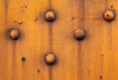 Yellow Metal. Close-up of grungy and yellow rusty metal with rivets Royalty Free Stock Photography