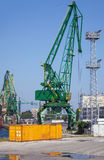 Yellow metal cargo container and green crane Stock Photos