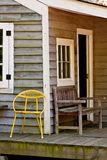 Yellow Metal Chair on an Old Bungalow Porch. An old metal chair and bench on a bungalow porch Stock Images