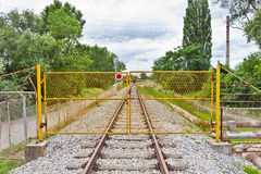 Yellow metal fence across the railroad Stock Images