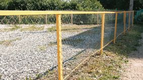 Yellow metal fence in the Park. Fenced area covered with pebbles. Yellow metal fence in the Park. Fenced area covered with pebbles stock footage
