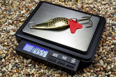 Yellow metal fishing bait for a spinning with pocket scale on the stony ground Stock Photography