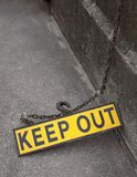 A yellow metal fluorescent keep out sign on a rusty metal chain on concrete Stock Images
