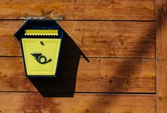 Yellow metal mailbox on a wooden wall. A series of pictures stock photo