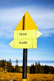 Yellow metal Road sign board.love ,hate. Yellow metal Road sign board in the mountain royalty free stock photos