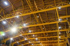 Yellow metal structure on roof with lamp lighting in storehouse royalty free stock images