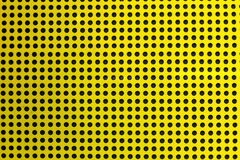 Yellow metal texture of holes over a black background (selective Stock Photography