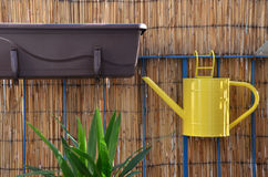 Yellow metal watering can hang on balcony railing, bamboo fence in background. Yellow metal watering can (pot) hang on balcony railing, bamboo fence in Stock Photography