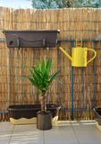 Yellow metal watering can hang on balcony railing, bamboo fence in background. Yellow metal watering can (pot) hang on balcony railing, bamboo fence in Stock Images
