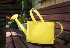 Yellow Metal Watering Can on a Wooden Garden Bench. Stock Photos