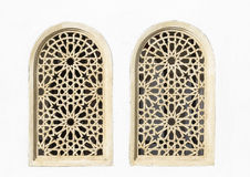 Yellow metallic windows with patterns on a white wall. Two yellow metallic windows with patterns on a white wall Stock Photography
