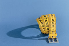 Yellow meter belt slimming on a blue Royalty Free Stock Image