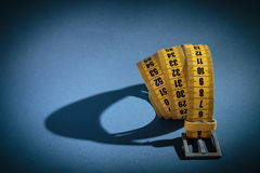 Yellow meter belt slimming on a blue Stock Photo