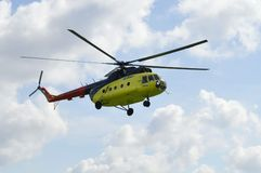 The yellow MI-8 helicopter flies against clouds. Royalty Free Stock Photos