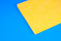 Yellow microfiber duster. Yellow microfiber kitchen duster on blue background Royalty Free Stock Photography
