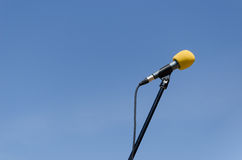 Yellow microphone on blue sky background Royalty Free Stock Image