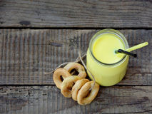 Yellow milk drink cocktails and a bunch of small bagels on a wooden background. Stock Photos