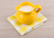 Yellow milk jug, napkin on wooden table Royalty Free Stock Image