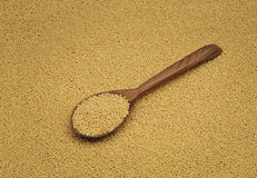 Yellow millet groats with wooden spoon Stock Photo