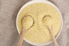 Yellow millet seeds. In a wooden bowl on the table Stock Photography