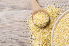 Yellow millet seeds. In a wooden bowl on the table Royalty Free Stock Photography