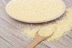 Yellow millet seeds. In a wooden bowl on the table Stock Photo