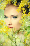 Yellow mimosa. Portrait of a beautiful girl with mimosa flowers. Spring stock image