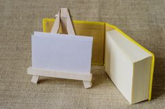 A yellow mini-notebook and a small wooden easel. Royalty Free Stock Image