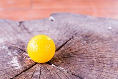 Yellow Miniature Golf Ball On Wood Background. Royalty Free Stock Images