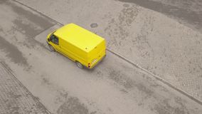 Yellow minibus moving along asphalt road. Yellow passenger van driving on road