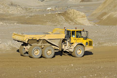 Yellow mining dump truck. A yellow dump truck is driving in a mine royalty free stock photography