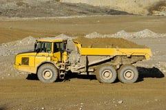 Yellow mining dump truck. A yellow dump truck is driving in mine stock photos