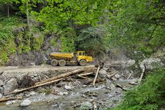 Yellow mining dump truck on forest road Royalty Free Stock Image